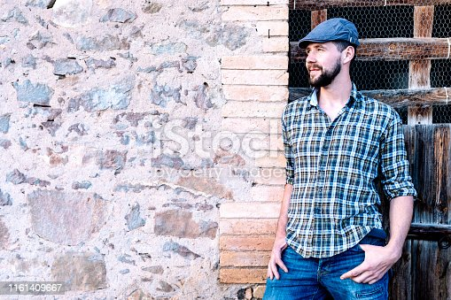 istock Casual young man standing with his back against a brick wall while looking away 1161409667