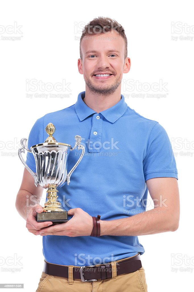 casual young man with trophy in hands stock photo