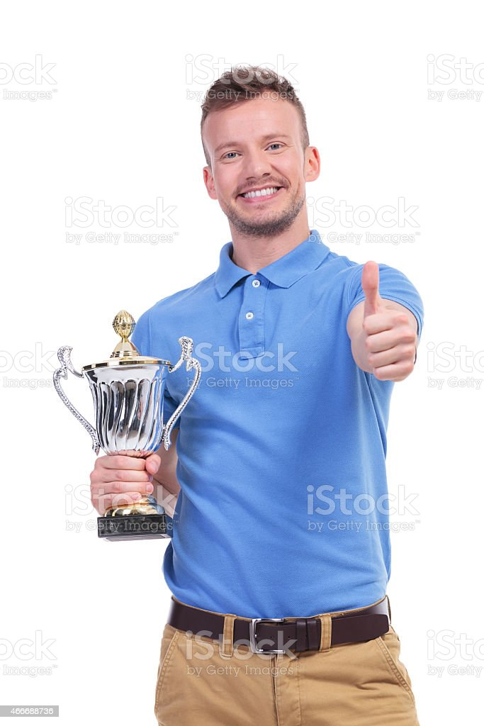 casual young man with trophy shows thumb up stock photo