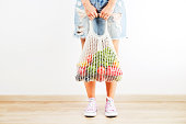 istock Casual young woman hands holding bunch of different fruits and vegetables in recyclable string sack. 1030424854