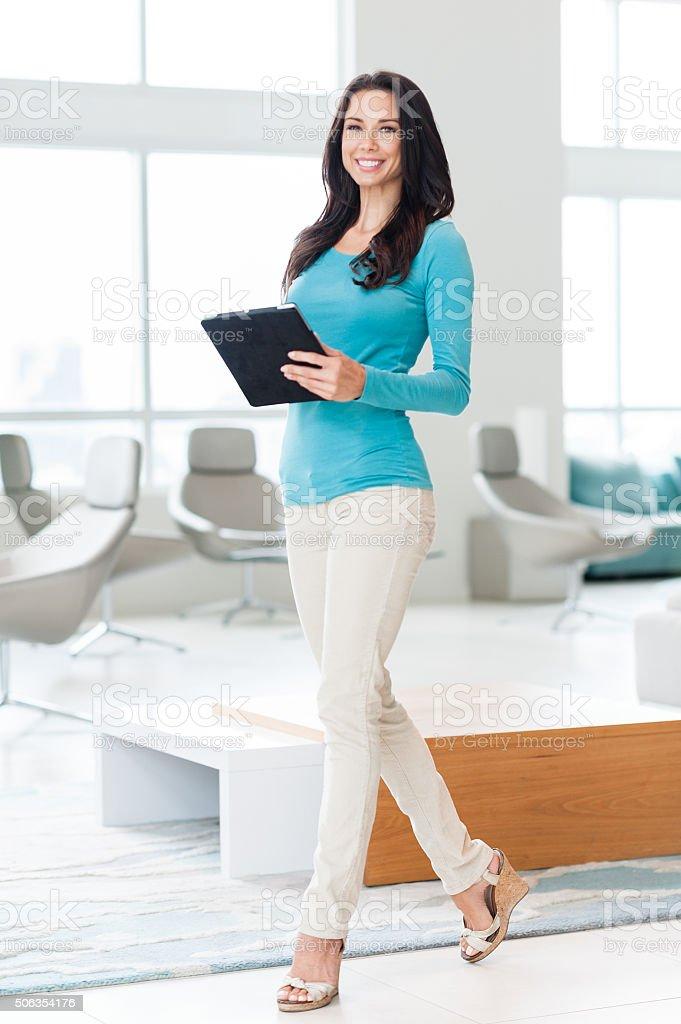 Twenty-something female woman with digital tablet in showcase...