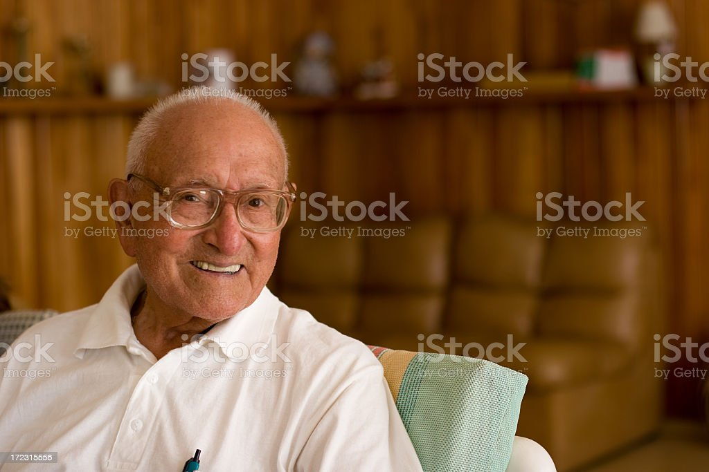 Casual-looking elderly man lounging at home stock photo