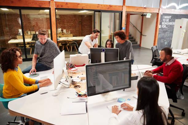 Gekleicht gekleidetes Business Team arbeitet an den Desken im modernen Open Plan Office – Foto