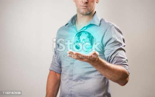 istock Casually dressed businessman holding virtual projection of the world in his hand 1153182538