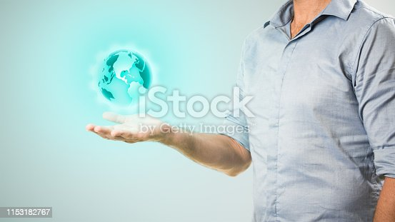 istock Casually dressed businessman holding virtual projection of the world in his hand 1153182767