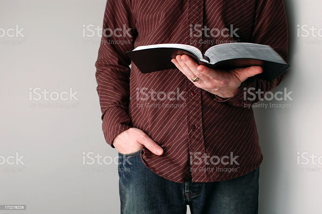 Casually Dressed Christian Guy Holding an Open Bible stock photo