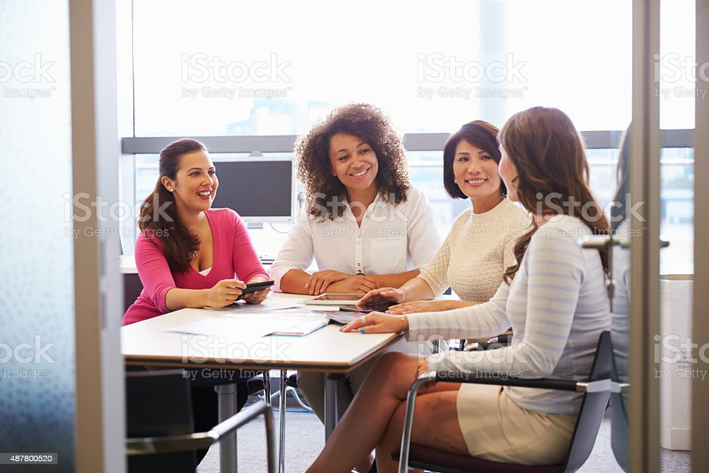 Casually dressed female colleagues talking in a meeting room stock photo