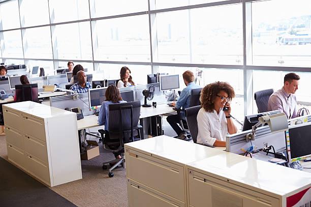 casually dressed workers in a busy open plan office - fullpackad bildbanksfoton och bilder