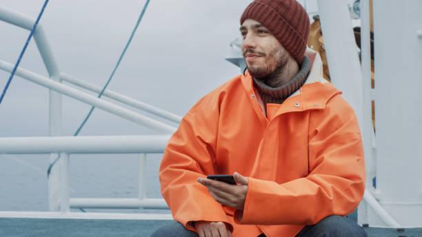 船上旅行中に携帯電話を使用してカジュアルな服を着た漁師。 - 漁師 ストックフォトと画像