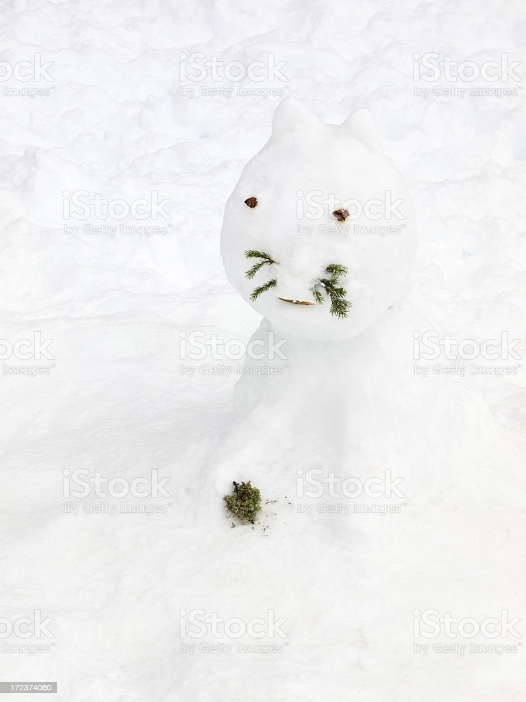 A cat made out of snow with pine needles for whiskers. royalty-free stock photo