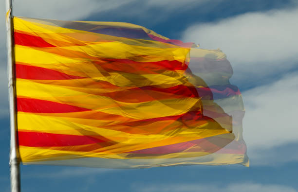 Catalan flag A double exposure shot of a large sunlit Catalan flag against a blue sky catalonia stock pictures, royalty-free photos & images