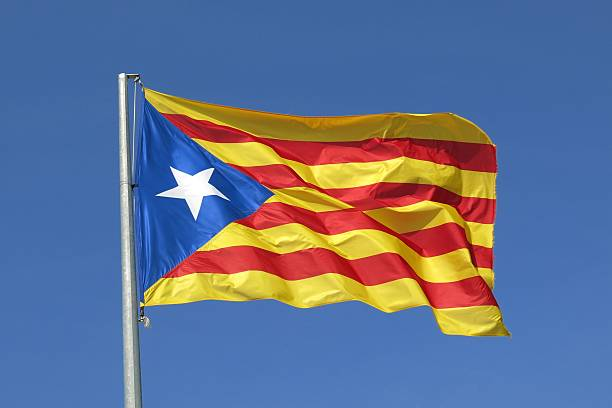 Catalan flag separatist independence flag waves in blue sky The Catalan separatist independence flag waves proudly in a cloudless blue sky catalonia stock pictures, royalty-free photos & images