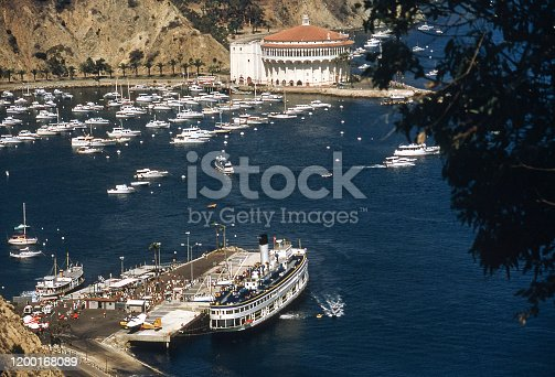 SS Catalina steam ferry docked in Avalon Bay, Catalina Island, California in September 1971. Passengers disembarking. Catalina Casino in background. The ferry was nicknamed The Great White Steamer and was in service from Los Angeles to Catalina Island from 1924 to 1975. Scanned film.