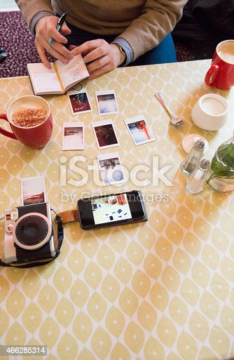 A photographer cataloguing his imagery in a coffee shop.