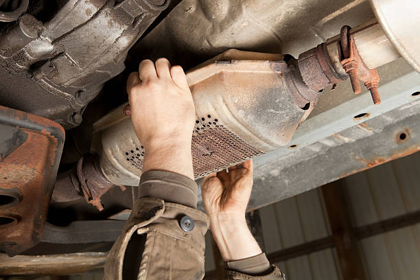 Catalytic Converter Removal at a Salvage Yard stock photo
