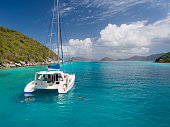 istock catamaran anchored with peope relaxing by Lovango Cay, Virgin Islands 1289894418