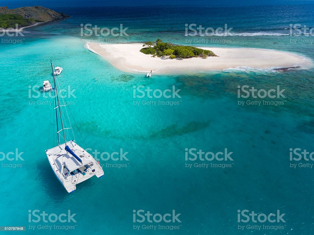 Catamaran at anchor in front of deserted island stock photo