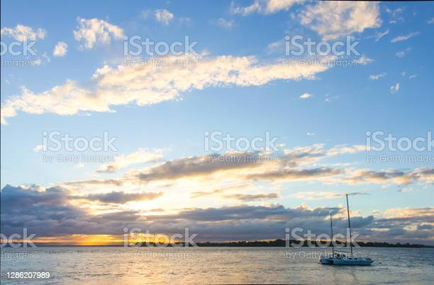 Photo of Catamaran sailboat in water at sunset with sun breaking though clouds on horizon