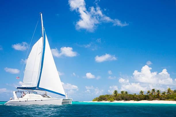 catamaran sailing close by a tropical island in the Caribbean