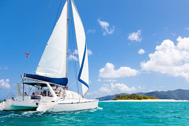 catamaran sailing close by a tropical island in the caribbean - katamaran bildbanksfoton och bilder