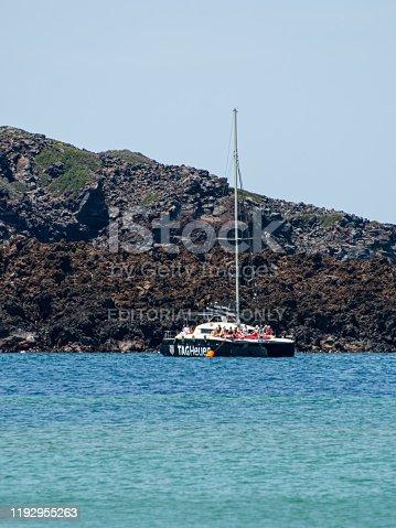Nea Kameni Island, Greece - July 16 2019:   A catamaran, sponsored by watch company Tag Heuer, anchored off the bassalt rocks of Nea Kameni island in the Aegean Sea