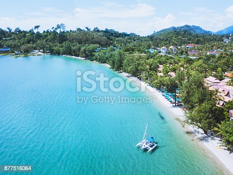 istock catamaran with sail anchored on beautiful tropical beach of Koh Chang island, Thailand 877516064