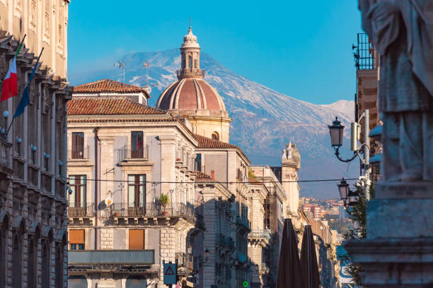 Catania and mount Etna, Sicily, Italy Dome of church and the main street via Etnea, volcano Etna on the background, Catania , Sicily, Italy. catania stock pictures, royalty-free photos & images