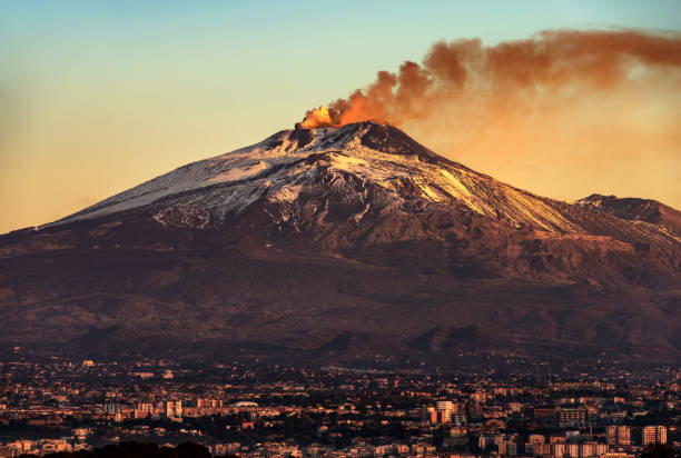 Catania and Mount Etna Volcano in Sicily Italy Mount Etna Volcano with smoke at dawn and the Catania city, Sicily island, Italy, Europe volcano stock pictures, royalty-free photos & images