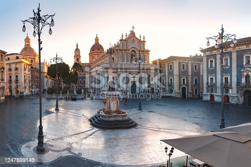 The first sunray on Piazza Duomo in Catania and the Cathedral of Santa Agatha and Liotru, symbol of Catania at sunrise, Sicily,