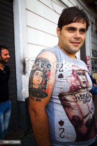Catania, Sicily: A man tattooed with the patron saint of Catania, Sant'Agatha (Saint Agatha) in downtown Catania. Close-up shot.