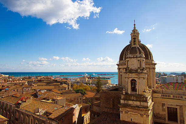 Catania, Sicily: Old Town Panorama with Cathedral Cupola and Sea Catania, Sicily: Beautiful old town panorama with vibrant orange tile roofs; the cupola and clock tower of Duomo di Sant'Agata is in the foreground and a turquoise sea (and Catania's harbor) and blue sky (with a puffy cloud) in the background. Copy space in the sky. The baroque Cathedral of Saint Agatha was constructed in the 18th century. catania stock pictures, royalty-free photos & images