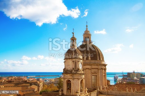 Catania, Sicily: Beautiful old town panorama with vibrant orange tile roofs; the cupola of the 18th-century Duomo di Sant'Agata is in the foreground and a turquoise sea and harbor in the background.