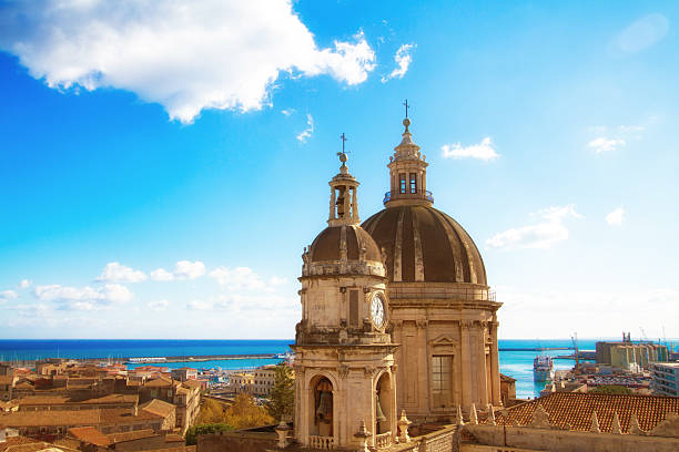 Catania, Sicily: Old Town Panorama with Cathedral Cupola and Sea Catania, Sicily: Beautiful old town panorama with vibrant orange tile roofs; the cupola of the 18th-century Duomo di Sant'Agata is in the foreground and a turquoise sea and harbor in the background. catania stock pictures, royalty-free photos & images