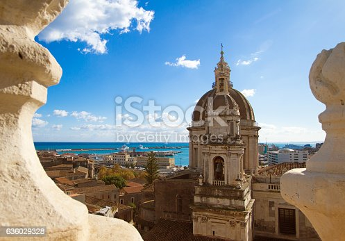 Catania, Sicily: Beautiful old town panorama with the cupola of the 18th-century Duomo di Sant'Agata and a turquoise sea framed (in the foreground) by two baroque architectural flourishes.