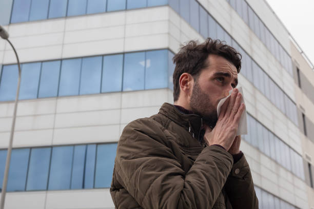 Catch a cold concept with people stills. Bearded caucasian man wearing a coat sneezing his nose using a paper tissue outdoors with a city building winter background. Ill workers going to work. respiratory disease stock pictures, royalty-free photos & images