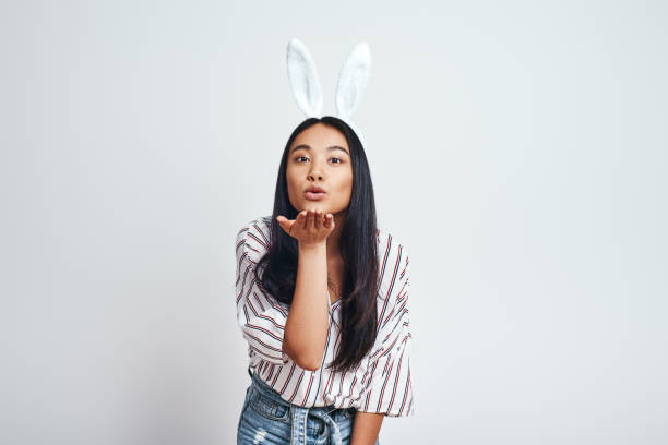 b1e7e913bad ... white background stock photo. Catch. Close up of cute young Asian woman  in bunny ears and casual clothes blowing