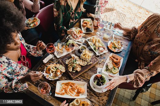 Group of multi-ethnic friends sharing multiple food dishes served on white plates and rustic wooden platters alongside quirky teacups and glasses of wine.