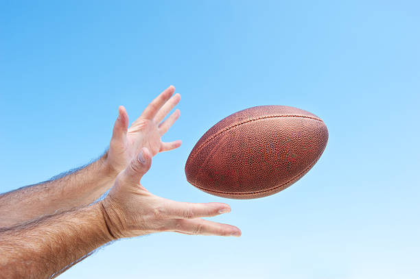 Catching a football A football player catches a spiral pass.  Clear sky good area for placing copy. catching stock pictures, royalty-free photos & images