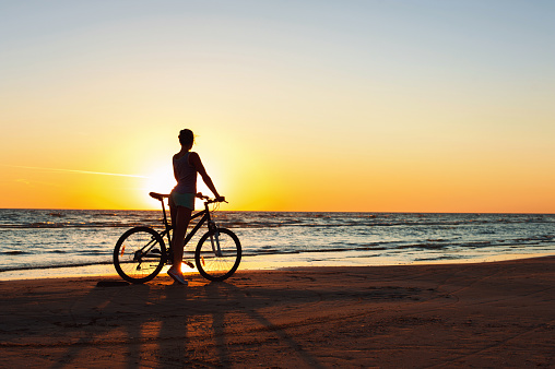 Catching a moment in time. Sporty woman cyclist at sunset