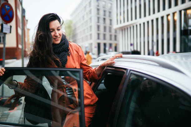catching a ride share in Berlin Young commuter woman catching a car ride share service in Berlin. She is smiling, wearing a fashionable coat, entering the vehicle. entering stock pictures, royalty-free photos & images