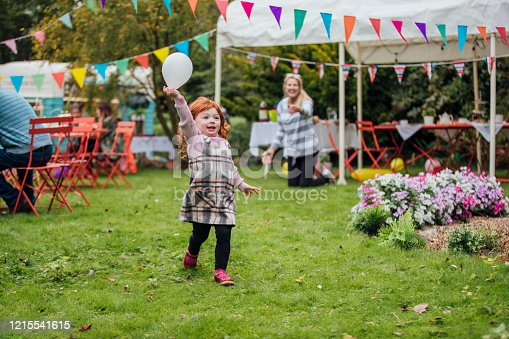 A young Caucasian redhead girl enjoys playing with a balloon at a garden party as she runs towards the camera. Adults are sat talking in the background and looking at the children. There is a food truck in the background and a marquee and colorful bunting fill the garden.
