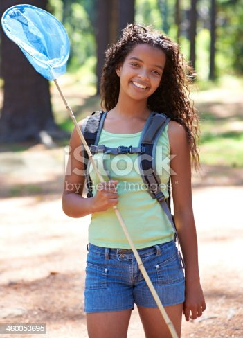 A young girl with a butterfly net standing in a forest