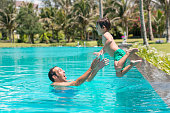 Man catching his son who is jumping into the pool