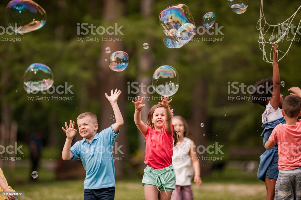 Catching rainbow bubbles in the park! royalty-free stock photo