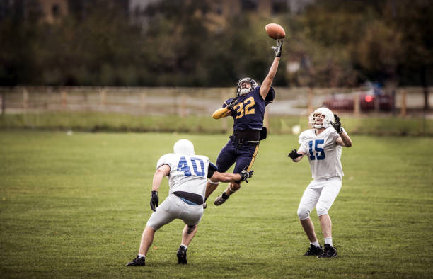 Catching the ball on American football match! Determined American football player catching the ball between his rivals on a match at playing field. wide receiver athlete stock pictures, royalty-free photos & images