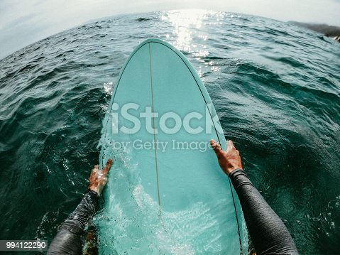First person point of view photo of a surfer floating in the ocean while catching the waves on his surfboard