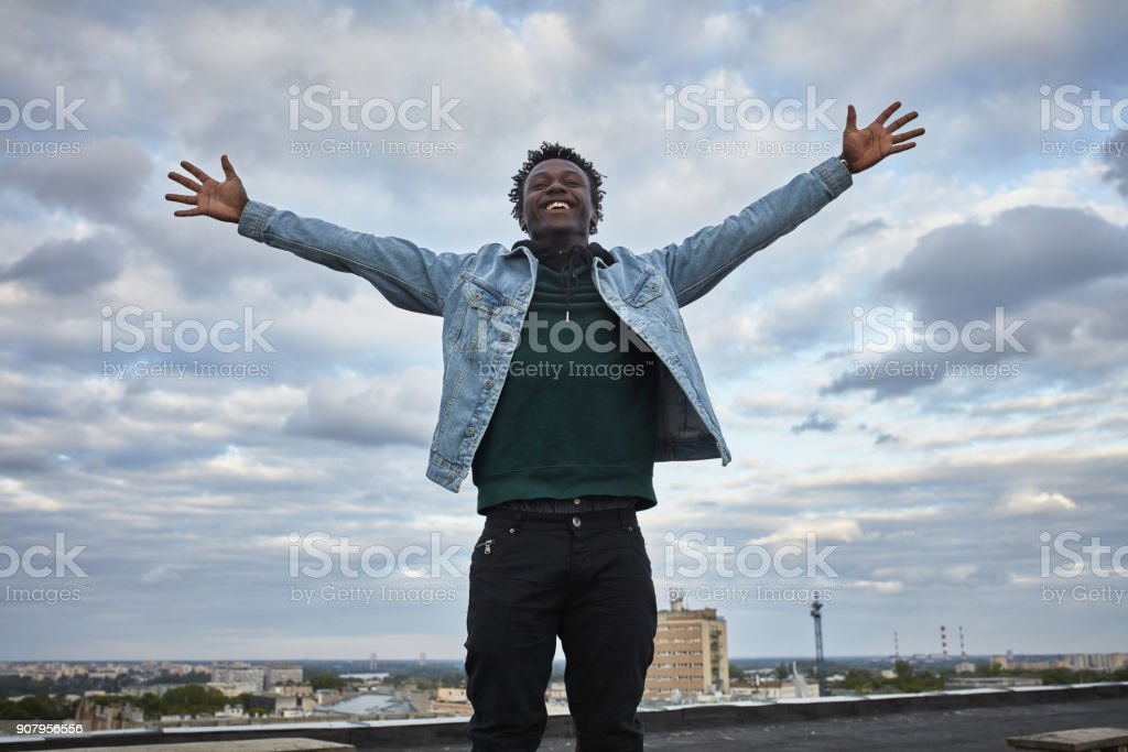 Catching the wind with arms outstretched. African man keeping balance on the roof stock photo