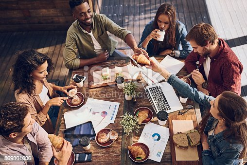 Shot of a group of creative workers having a meeting over lunch in a cafe