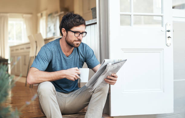 Catching up on the latest news Cropped shot of a handsome young man enjoying his coffee while reading the morning paper bachelor stock pictures, royalty-free photos & images