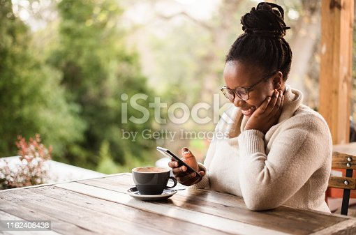 Shot of a young african woman reading text message on mobile phone and smiling while sitting in a coffee shop